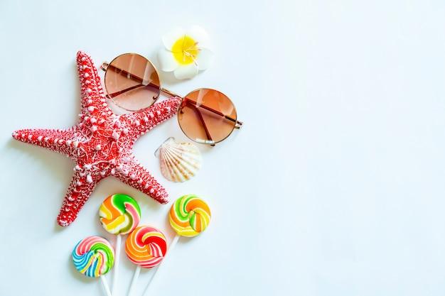 Étoile de mer, lunettes de soleil, sucettes et coquille sur tableau blanc avec espace libre.