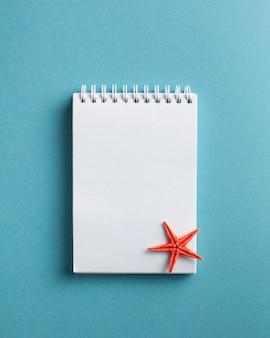 Étoile de mer rouge sur un cahier blanc vierge sur bleu