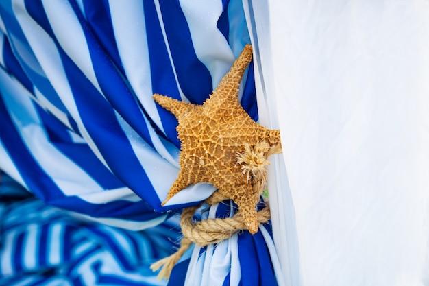 Étoile de mer séchée sur les rideaux bleus et blancs. décor sur la fête du temps de la mer.