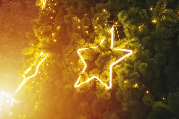 Étoile d'or sur un arbre de noël au fond de la nuit.