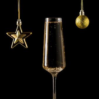 Étoile d'or et ballon et un verre de vin mousseux sur fond noir. une boisson alcoolisée populaire.