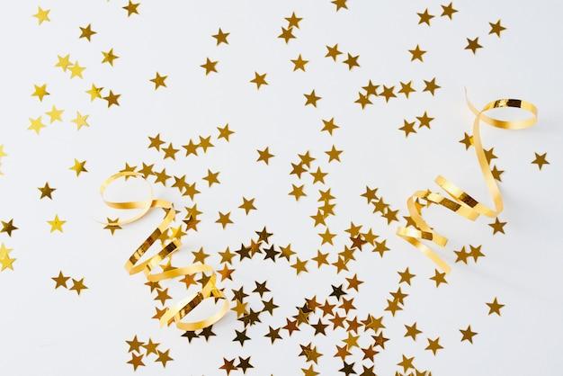 Étoile d'or scintillant sur blanc.