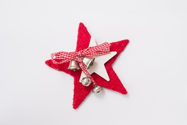 Étoile rouge de noël avec des cloches isolé sur blanc, décor de nouvel an