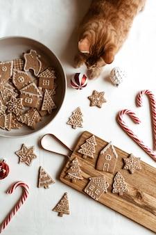 Étoiles de biscuits au gingembre maison, sapins, maisons sur planche à découper en bois, bonbons bâton et beau chat rouge mignon. mise à plat, composition de noël vue de dessus.