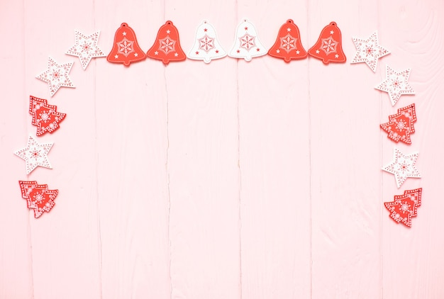 Étoiles blanches et rouges et cadre d'arbres de noël sur une surface en bois rose