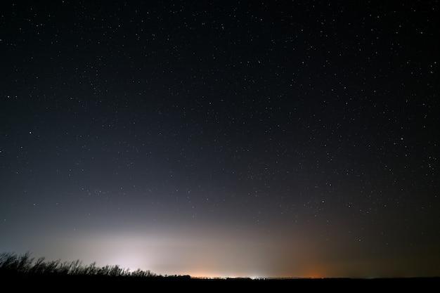 Des étoiles brillantes dans le ciel nocturne avec l'éclairage des réverbères de la ville