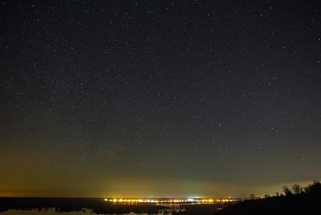 Étoiles brillantes du ciel nocturne contre la surface de la surface lisse du lac