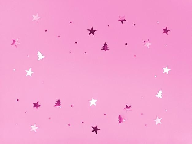 Étoiles de confettis et arbres étincelants sur fond rose.