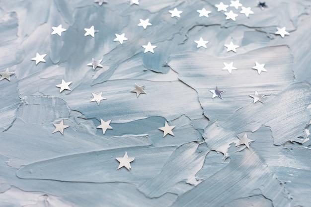 Étoiles de confettis de feuille d'argent à la mode sur fond blanc et bleu. abstrait d'hiver. célébration de noël, vacances et concept de rêves
