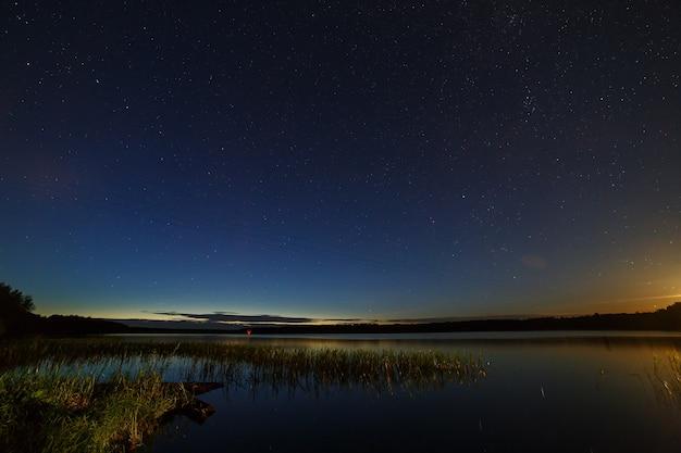 Les étoiles dans le ciel nocturne au-dessus de la rivière.