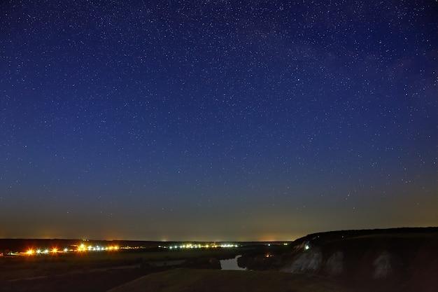 Étoiles dans le ciel nocturne au-dessus de la vallée de la rivière et de la ville