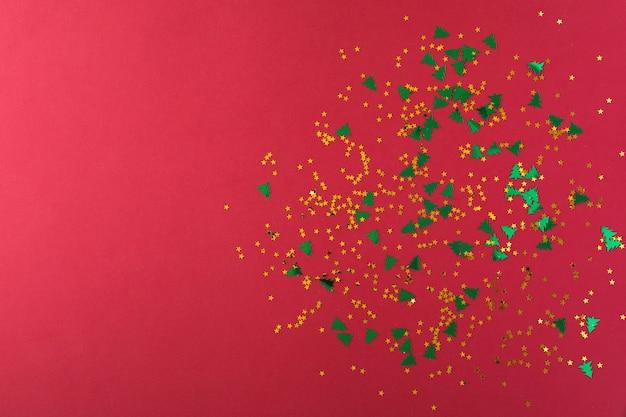 Étoiles dorées et arbres de noël verts en forme de cadre de confettis sur fond rouge. vue de dessus, mise à plat