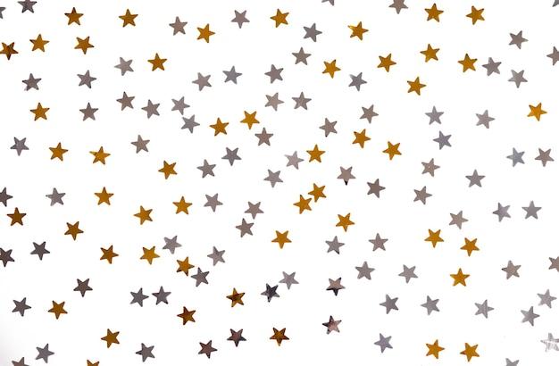 Des étoiles dorées et argentées brillent sur un fond blanc isolé.
