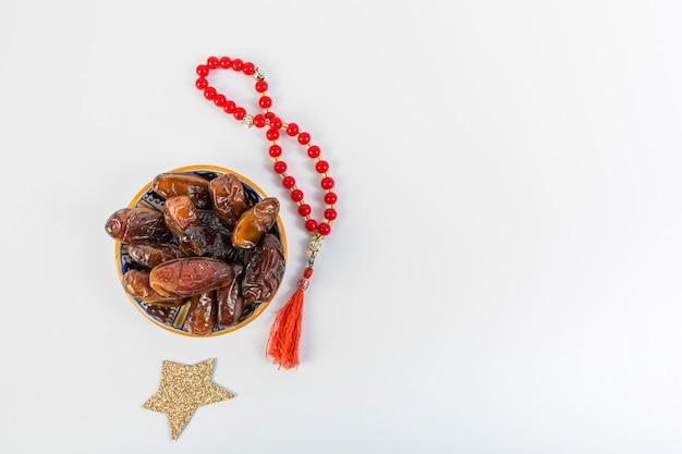 Étoiles dorées avec bol de dattes juteuses et perles de prière rouges sur fond blanc