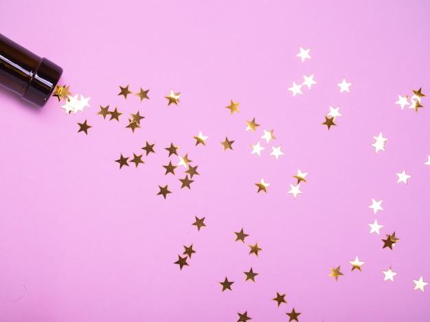 Des étoiles dorées coulent de la gorge de la bouteille pour la nouvelle année.