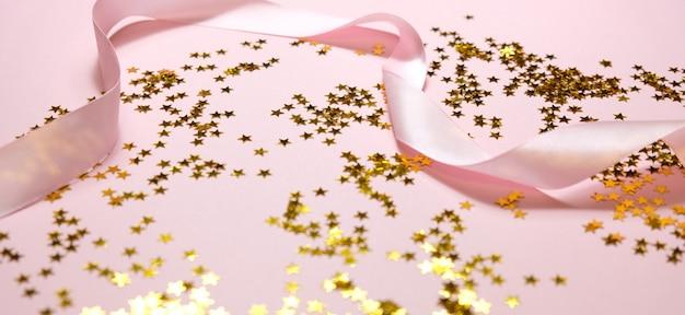 Étoiles dorées et ruban rose