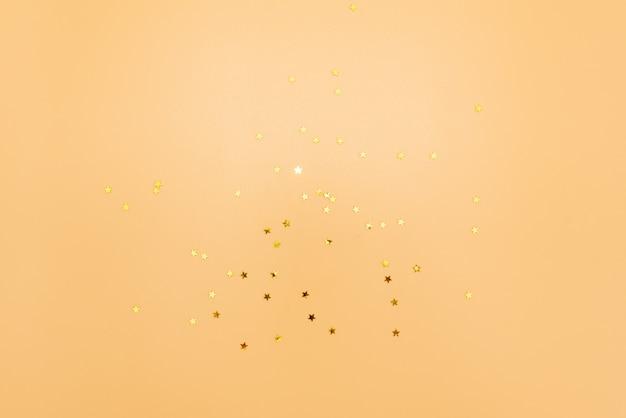 Des étoiles dorées scintillent sur fond rose. toile de fond pastel de vacances.