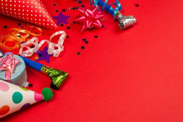 Des étoiles dorées et violettes festives de confettis et un cadeau, des chapeaux d'anniversaire sur fond rouge. espace pour le texte ou la conception.