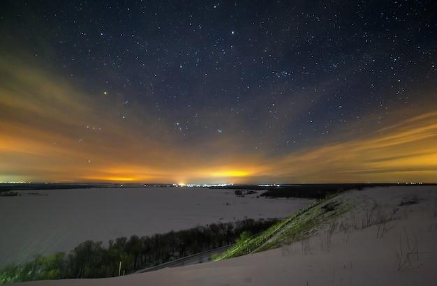 Les étoiles du ciel nocturne sont cachées par les nuages. paysage d'hiver enneigé au crépuscule. ville dans la vallée.