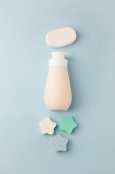 Étoiles éponge; barre de savon et distributeur sur fond bleu