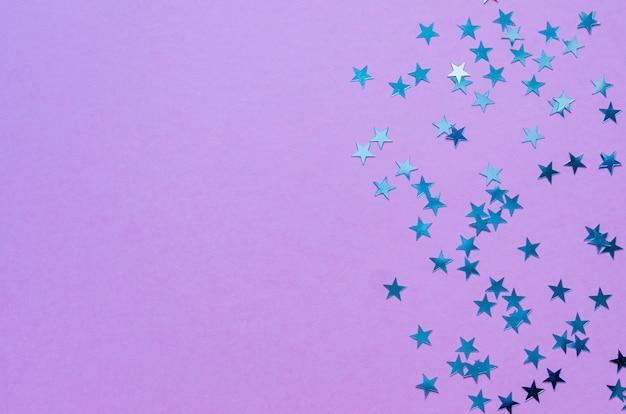 Étoiles holographiques sur fond violet branché. toile de fond festive. vue de dessus. espace de copie.