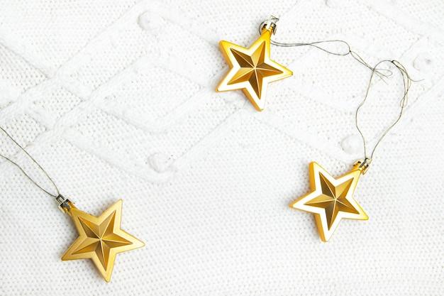 Les étoiles de jouets de noël sont dorées. jouets de noël dorés. tissu tricoté blanc. nouvel an et vacances de noël. mise en page de noël sur le dessus. article sur les vacances. copier l'espace