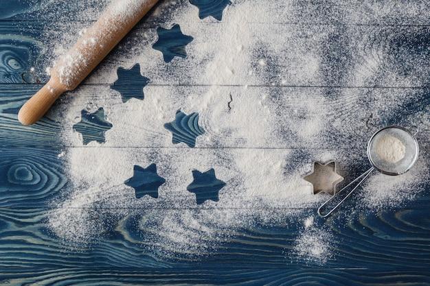 Étoiles de noël sur fond de farine avec espace copie. la farine blanche ressemble à de la neige. vue de dessus