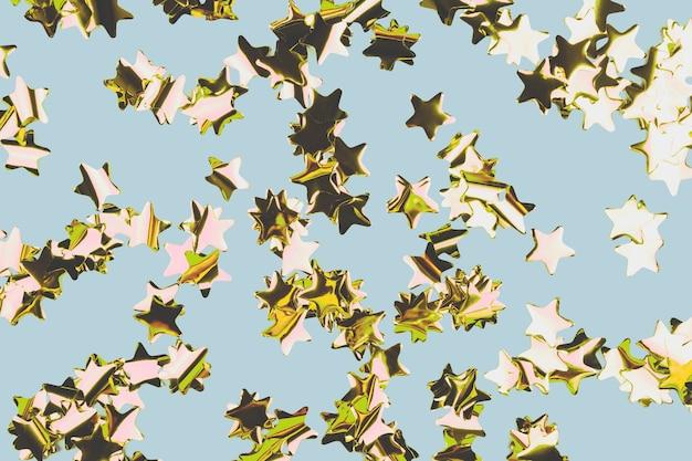 Étoiles d'or confettis fond rétro bleu festif célébrant l'espace de copie de noël ou d'anniversaire