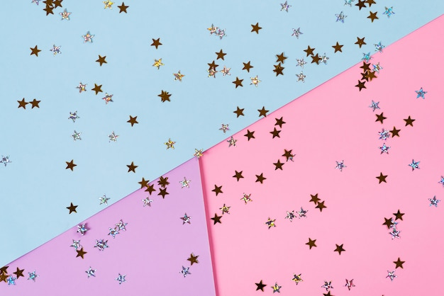 Étoiles d'or sur fond bleu rose. thème d'anniversaire ou de fête. concept minimal. mise à plat. vue de dessus.