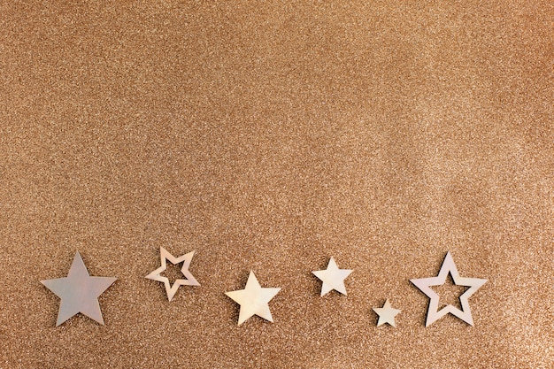 Étoiles d'or rose et fond brun clair de paillettes. décoration de fête de vacances.