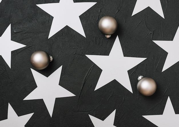 Étoiles en papier avec des boules brillantes sur la table