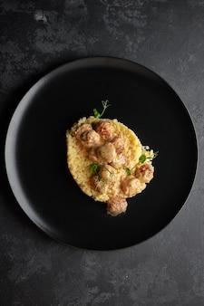 Étoiles de pâtes bouillies aux boulettes de viande et microgreen, sur fond noir