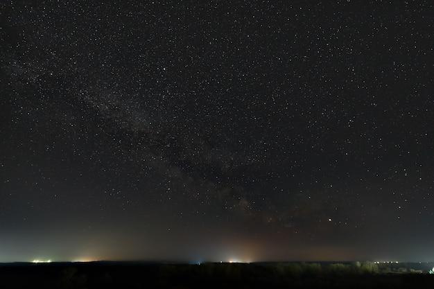 Étoiles de la voie lactée dans le ciel nocturne. la pollution lumineuse des lampadaires au-dessus de l'horizon.