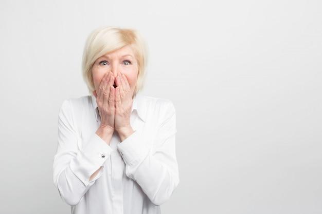 Étonnamment belle et magnifique, une vieille femme garde sa main sur la bouche, montrant qu'elle est très surprise.