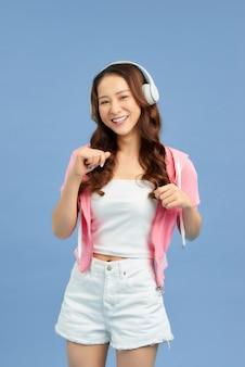 Étonnante charmante jeune femme en short en jean sur fond bleu coloré. danser, écouter de la musique avec des écouteurs