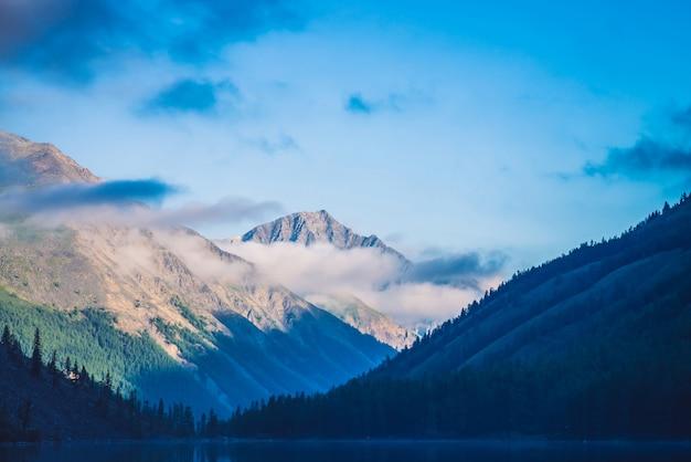 Étonnantes silhouettes bleues des montagnes sous le ciel bleu nuageux.