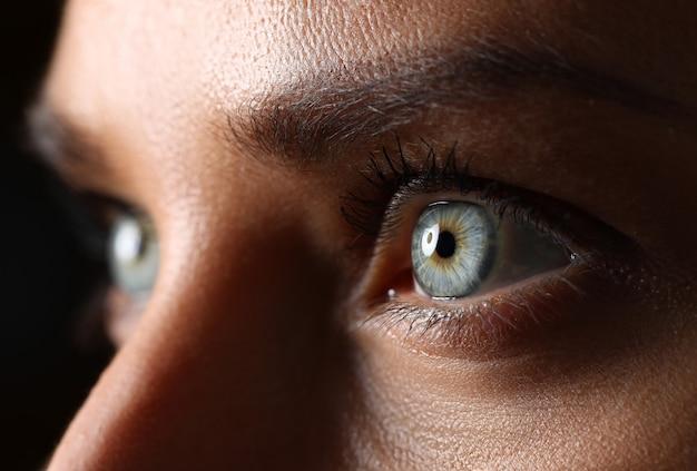 Étonnantes yeux de couleur verte et bleue féminine en gros plan technique de faible luminosité