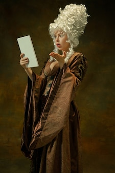 Étonné à l'aide de la tablette. portrait de jeune femme médiévale en vêtements vintage marron sur fond sombre. modèle féminin en tant que duchesse, personne royale. concept de comparaison des époques, moderne, mode, beauté.