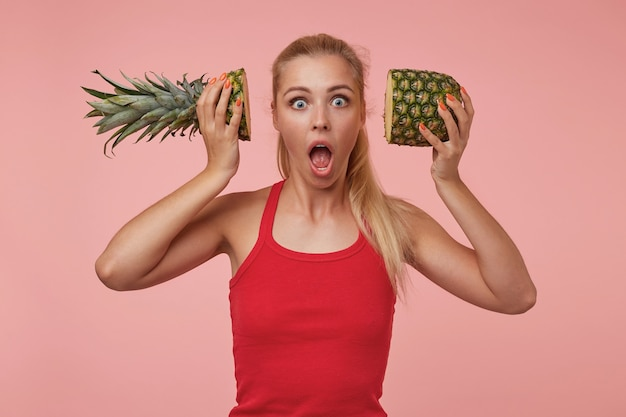 Étonné belle femme aux cheveux longs blonds tenant les moitiés d'ananas près de ses oreilles, regardant avec de grands yeux et bouche ouverte