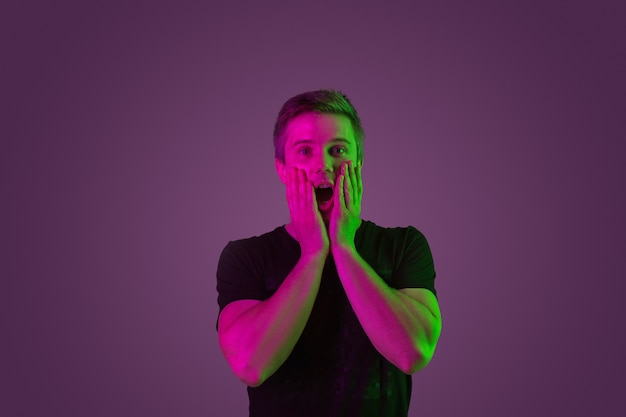 Étonné, choqué, interrogé. portrait de l'homme caucasien sur fond de studio violet en néon. beau modèle masculin en chemise noire. concept d'émotions humaines, expression faciale, ventes, publicité.