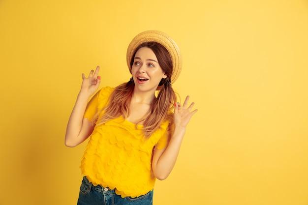Étonné, choqué, mignon. portrait de femme caucasienne sur fond de studio jaune. beau modèle féminin au chapeau. concept d'émotions humaines, expression faciale, ventes, publicité. l'été, les voyages, la station balnéaire.