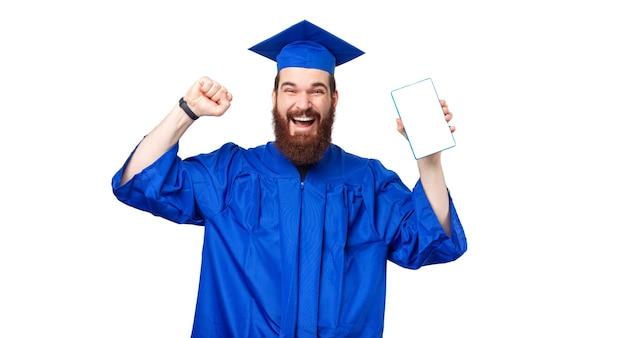 Étonné étudiant homme vêtu d'une robe bleue et célébrant tout en tenant une tablette avec écran blanc