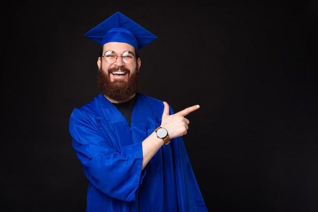 Étonné homme étudiant barbu en baccalauréat bleu pointant vers l'extérieur