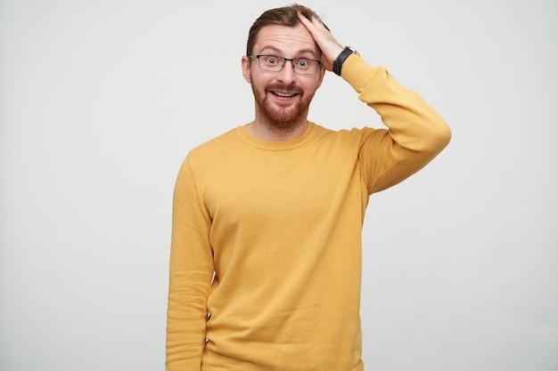 Étonné jeune beau mec barbu brune froissant ses cheveux courts avec la main et soulevant joyeusement les sourcils, portant des lunettes en position debout