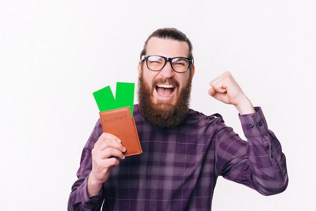 Étonné jeune homme barbu portant des lunettes et tenant un passeport avec des billets