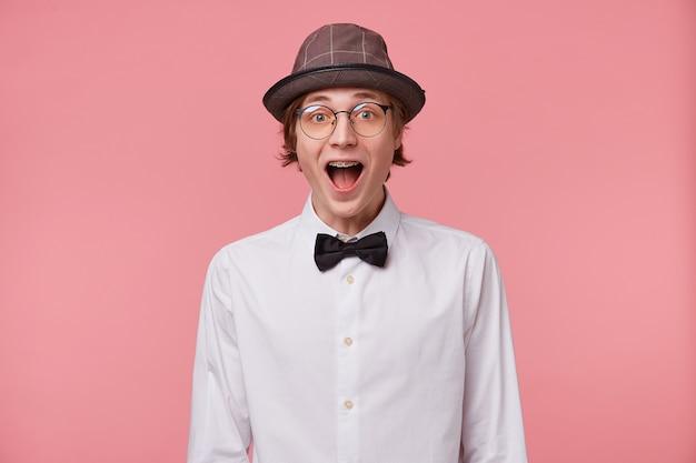 Étonné jeune homme en chemise blanche, chapeau et noeud papillon noir porte des lunettes a des accolades, a largement ouvert la bouche de surprise, rempli d'émotion, isolé sur fond rose