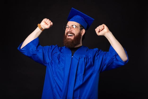 Étonné jeune homme étudiant célébrant et portant un baccalauréat bleu