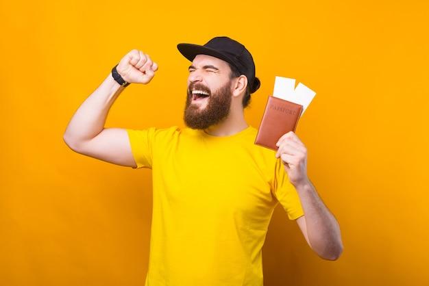 Étonné jeune homme hipster barbu célébrant des vacances et tenant un passeport avec des billets