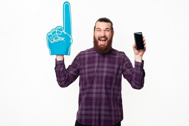 Étonné et joyeux jeune homme en pointage occasionnel avec un gant de ventilateur et montrant le smartphone