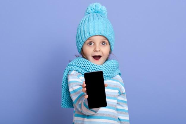 Étonné petite fille enfant portant un chapeau d'hiver avec pom pom montrant un écran blanc